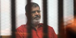 """CAIRO, EGYPT - JUNE 27: Former Egyptian President Mohamed Morsi, wearing a red uniform after Cairo Criminal Court sentenced him to death over a prison break in 2011, stands behind bars during the trial of him and ten others for allegedly """"espionage for Qatar"""" at Cairo Police Academy on June 27, 2015 in Cairo, Egypt. (Photo by Ahmed Omar/Anadolu Agency/Getty Images)"""